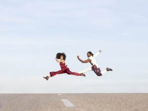 Two Dancers Leaping Across a Road